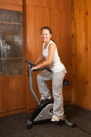woman exercise on spinning bicycle at home photo