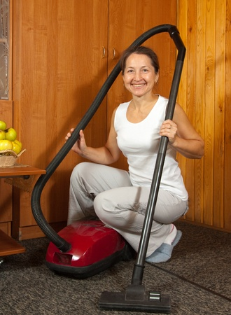 Photo of an attractive senior woman vacuuming her living room. photo
