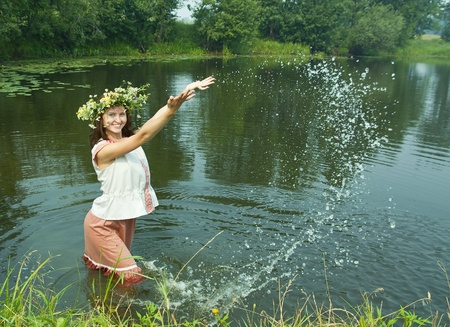 Pretty girl  in flower chaplet at river photo
