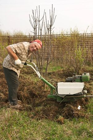 motor hoe: Adult man  plowing his spring yard with motor cultivator Stock Photo