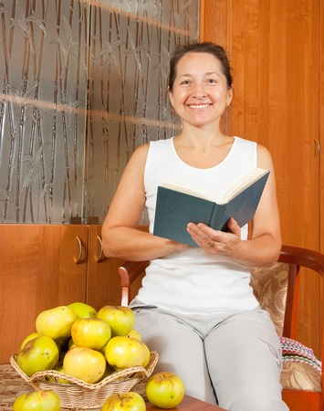 elegance woman reading bok near table with apples photo
