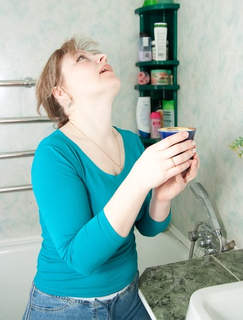 sicken: Young woman with glass of  medicine gargling