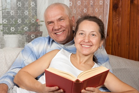 Portrait of a happy   couple reading in interior photo