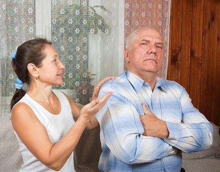mature couple having a fight, at home on sofa  photo