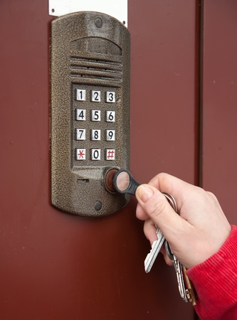 access control: Close-up oh womans hand with key of building intercom