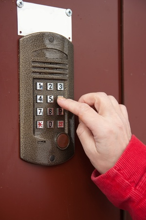 womans hand  using building intercom  buzzer outdoor in autumn Stock Photo