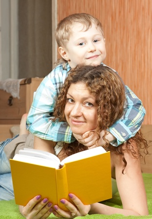 mother with her son reading book on sofa  photo