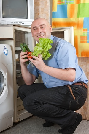 Happy man putting fresh vegetables into fridge at home photo