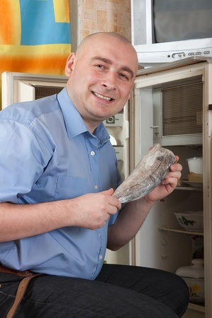 frost bound: man putting fresh frozen fish into fridge at home