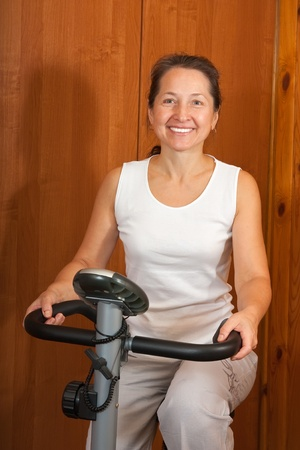 Woman working out indoors on a spinning bike photo
