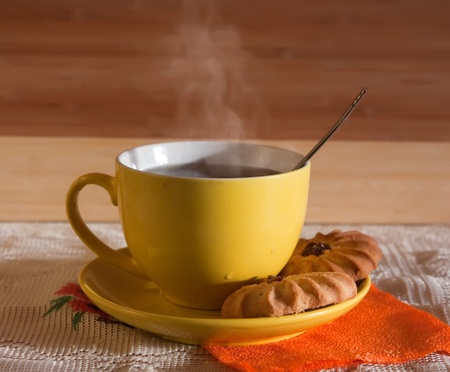 Cup of hot tea with steam on wooden background. Light tone. photo