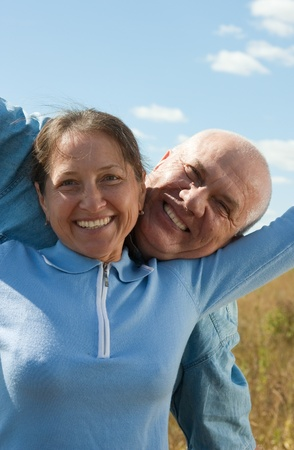 Happy senior couple going for a walk at summer day photo