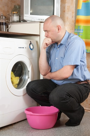 Young man loading the washing machine in kitchen