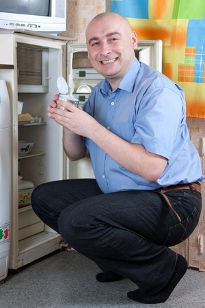frowy: man  holding her nose because of bad smell near fridge at home  Stock Photo