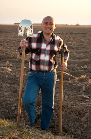 Happy man with spade and pitchfork at farm field photo