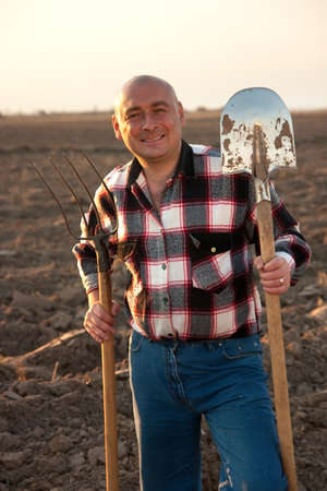 agricultural tools: Adult farmer with agricultural tools at field Stock Photo