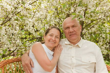 Portrait of an attractive mature couple,against white flowering trees photo