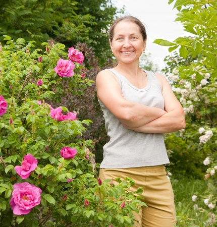 briar bush: Smiling adult woman with dogrose in her garden