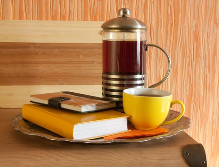 Cup of hot tea with steam on yellow book. Light tone. photo
