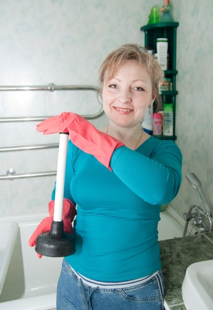 Adult woman with plunger in her bathroom photo
