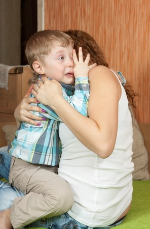 crying child: crying child and his careful mom in home interior Stock Photo