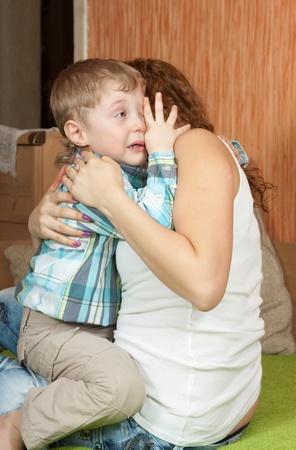 child crying: niño que llora y su madre en el cuidado interior de una casa