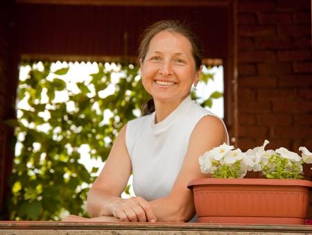 tuinhuis: Portret van mooie rijpe vrouw buiten in tuinhuisje