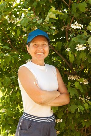 smiling adult woman near  snowball tree in her garden photo