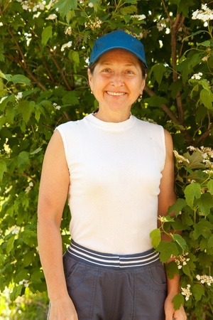 smiling adult woman with flowers of  snowball tree in her garden photo