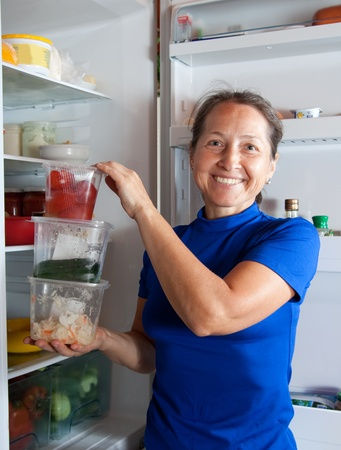 Ordinary woman taking something of the fridge  Stock Photo - 11280192