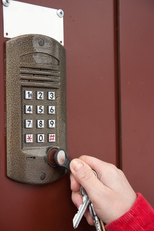 Close-up oh woman's hand with key of building intercom photo