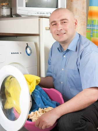 mid adult  man putting clothes in to washing machine and smiling Stock Photo - 11244707