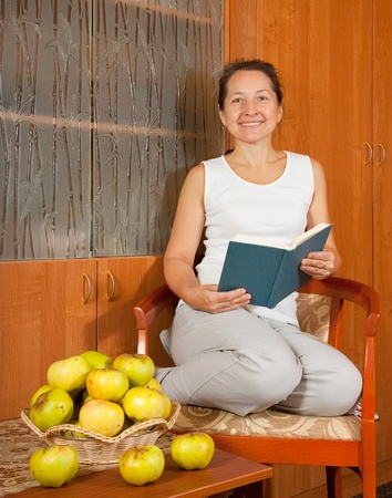 Happy woman with blue book sitting and smiling photo