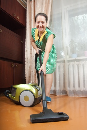 Portrait of mature lady in cleaning a living room floor photo