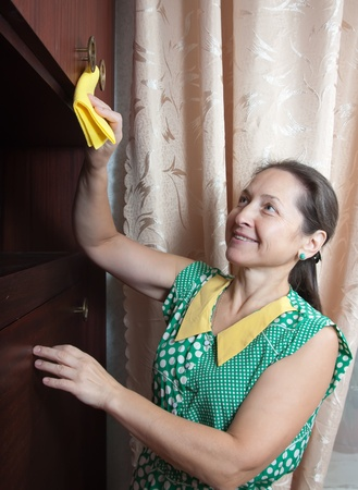 Mature woman cleans a furniture indoor Stock Photo