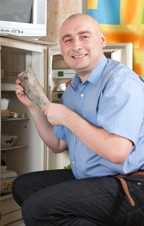 frost bound: man putting raw frozen fish into refrigerator  at home Stock Photo