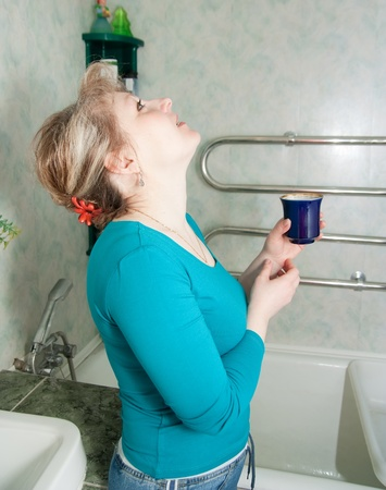 Brunette illness woman gargles her throat in bath