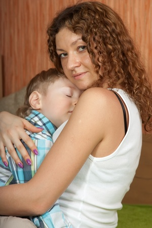 Mother comforts her young son photo