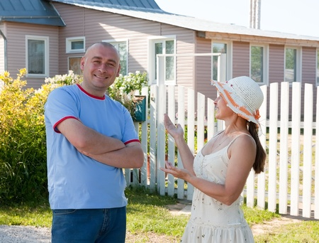 wicket gate: Hospitable adult man and mature woman in front of  house