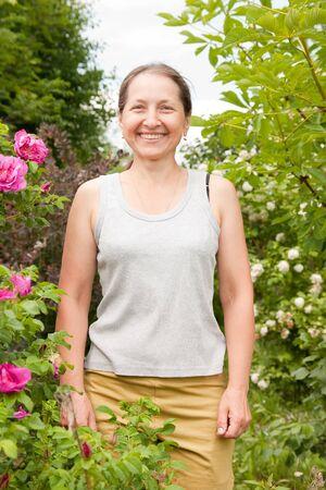 briar bush: Mature woman outdoor in blossoming garden
