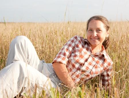 Mature woman  smiling against summer landscape photo