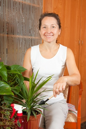 Mature woman sitting on chair and takes care of indoor plants photo