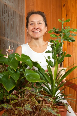 Mature woman holding flowers in  pot in house photo