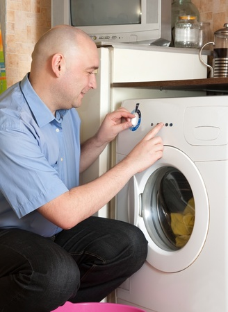 Young man loading the washing machine in kitchen photo