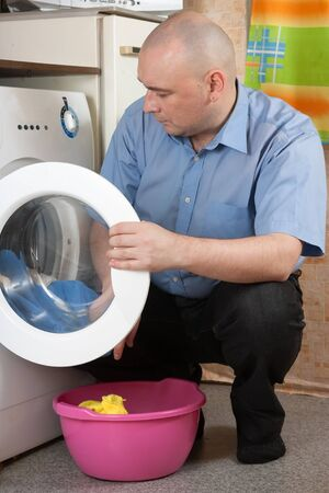 Man loading the washing machine at his home photo