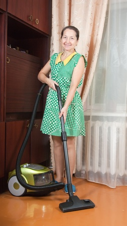 vaccuum: Smiling woman use vacuum cleaner in a living room
