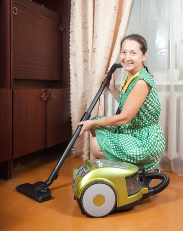 vaccuum: Cheerful expression worn by a well uniformed housekeeper  She is vacuuming the entry foyer into  home