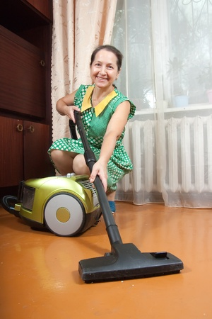 Photo of an attractive senior woman vacuuming her living room  photo
