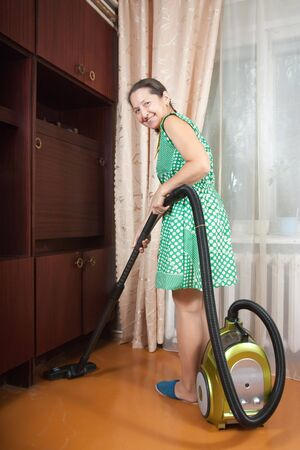 vaccuum: Photo of an attractive senior woman vacuuming her living room  Stock Photo
