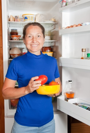 ordinary woman:  Ordinary woman taking something of the fridge